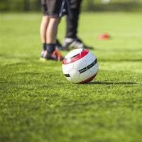 Un ballon de soccer sur un terrain de gazon devant de jeunes joueurs.
