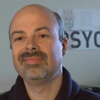 Un homme regarde par-delà la caméra. Derrière, une affiche avec le mot Psycho est collée au mur.