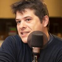 Le chef Stéphane Modat parle dans un studio de radio.