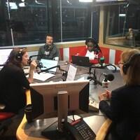 Une femme et trois hommes sont assis autour d'une table dans un studio de radio
