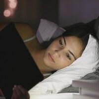Une jeune fille couchée regarde une tablette électronique.