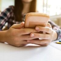 Un gros plan sur les mains d'une jeune fille qui tient un téléphone intelligent. Ses mains sont posées sur son pupitre d'école, par dessus un cahier ligné.