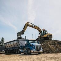 Un camion et une pelle mécanique sur une montagne de terre.