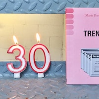Une bougie allumée qui indique 30 ans et un livre rose.