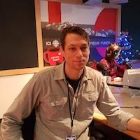 Un homme assis dans les studios radio de l'Émission Phare Ouest