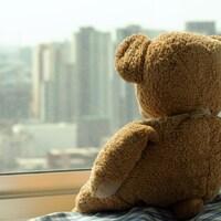 Un ourson en peluche triste regarde à l'extérieur.