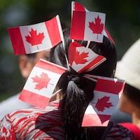 Une femme de dos avec six petits drapeaux du Canada plantés dans ses cheveux.