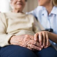 Une personne âgée est dans une chaise roulant et une femme plus femme lui tient la main.