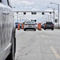 Des policiers parlent à des automobilistes sur le pont, entourés de cônes orange.