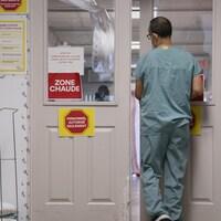 Un travailleur de la santé s'apprête à entrer dans une zone chaude d'un hôpital.