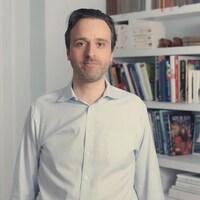 L'homme en chemise apparaît dans sa maison pour les besoins d'une vidéo promotionnelle.