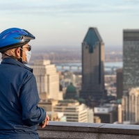 Sur le belvédère du mont Royal, un homme qui porte un casque de vélo et un masque regarde l'horizon.
