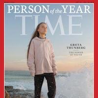 Greta Thunberg debout sur un rocher près de la mer.