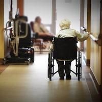 Une dame dans un fauteuil roulant dans le couloir d'un CHSLD