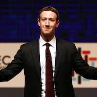 Mark Zuckerberg sourit en ouvrant les bras.