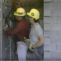 Deux électriciens coiffés de casques jaunes travaillent sur un système électrique.