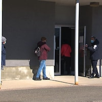 Des gens font la file à l'extérieur pour accéder au site de vaccination.