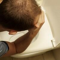 Un homme est accoudé sur la cuvette de sa toilette.