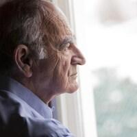 Un homme âgé regarde par la fenêtre.