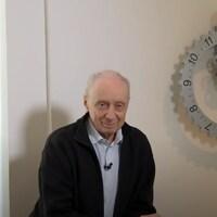 Le cinéaste et réalisateur Fernand Dansereau assis à côté d'une horloge.