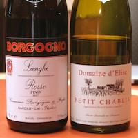 Deux bouteilles de vins rouge et blanc sur une table.