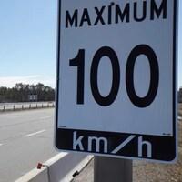 Une pancarte routière indiquant la vitesse maximale permise de 100km/h ainsi qu'un véhicule circulant sur une autoroute.