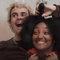 Deux personnes rigolent ensemble, tandis que l'une d'elles simule de vouloir tondre les cheveux de l'autre.