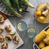 Vue de plongée d'une table avec des bouchées de maïs à la mexicaine, une limonade infusée au maïs et des épis de maïs assaisonnés.
