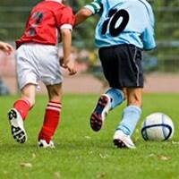 De jeunes joueurs de soccer courent derrière le ballon.