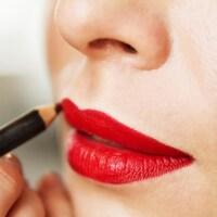 Une femme s'applique du crayon à lèvres.