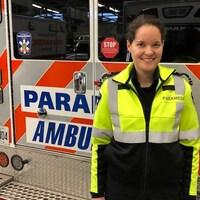 Dominique Arseneau pose devant une ambulance