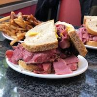 Un sandwich au pastrami avec une assiette de frites et un sandwich de boeuf salé en arrière-plan.