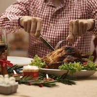 Un homme coupe une dinde sur une table décorée pour Noël.