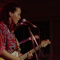 Image d'une guitariste dans le film Long Time Comin' de Dionne Brand.