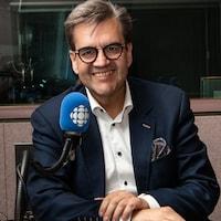 L'ex-maire de Montréal sourit à la caméra devant un micro dans un studio de radio.