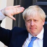 Boris Johnson lève la main en guise de salut.