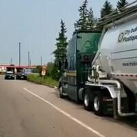 Un camion de transport arrêté sur une bretelle d'entrée d'une aire de service autoroutier.