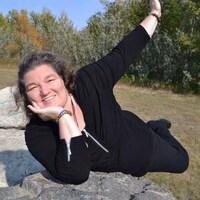 Angèle est couchée sur une grosse pierre.