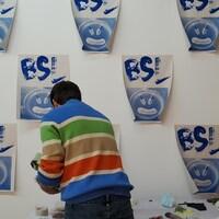 Un artiste devant un mur où sont collées plusieurs affiches sur lesquelles on peut lire BSL.
