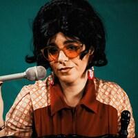 Une femme avec une perruque et de grandes lunettes teintées brunes tenant un micro.