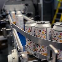 Des cannettes de bière alignées dans une machine qui met la bière en cannette.