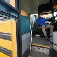 Un conducteur de bus scolaire est installé au volant et est équipé d'un couvre-visage.