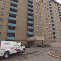 Une ambulance est stationnée devant un immeuble