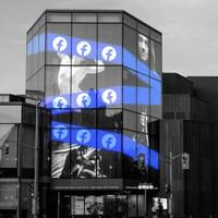 La façade de l'édifice du CNA affiche un bandeau avec le logo de Facebook.
