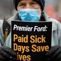 Un manifestant en tenue d'hiver tient une pancarte demandant au premier ministre Ford de mettre en place des congés de maladie payés.