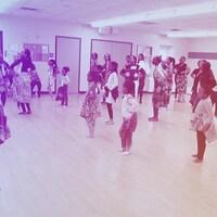 Une vingtaine d'enfants, d'adolescentes et d'adultes d'origine burundaise, les mains positionnées sur les hanches, semblent suivre les consignes données par des professeures dans une salle de danse avec un plancher de bois et un grand miroir.