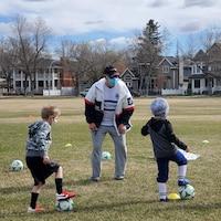 Des jeunes suivent les consignes de leur entraîneur sur un terrain de soccer.