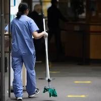 Une femme en tenue médicale déambule dans un bâtiment avec un balai en main.