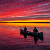 Un canot se trouve sur l'eau au coucher du soleil.