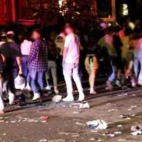 Des personnes rassemblées dans une rue, des détritus sont pare terre.